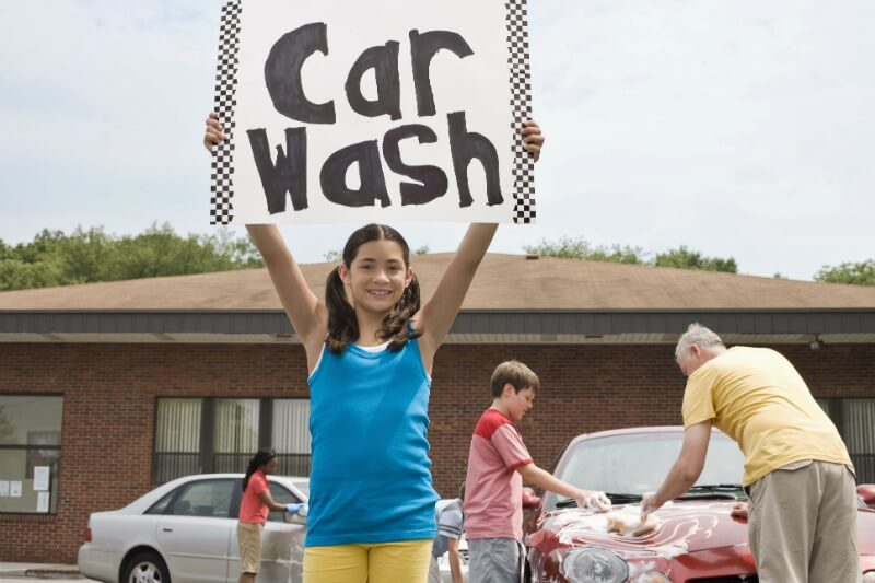 IMG: girl holding up sign for car wash