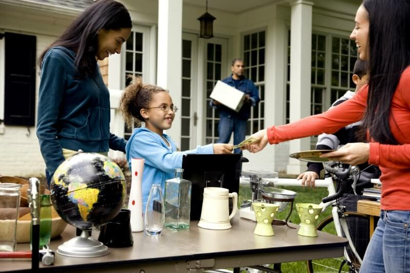 IMG: girl and woman exchanging money for goods at a yard sale