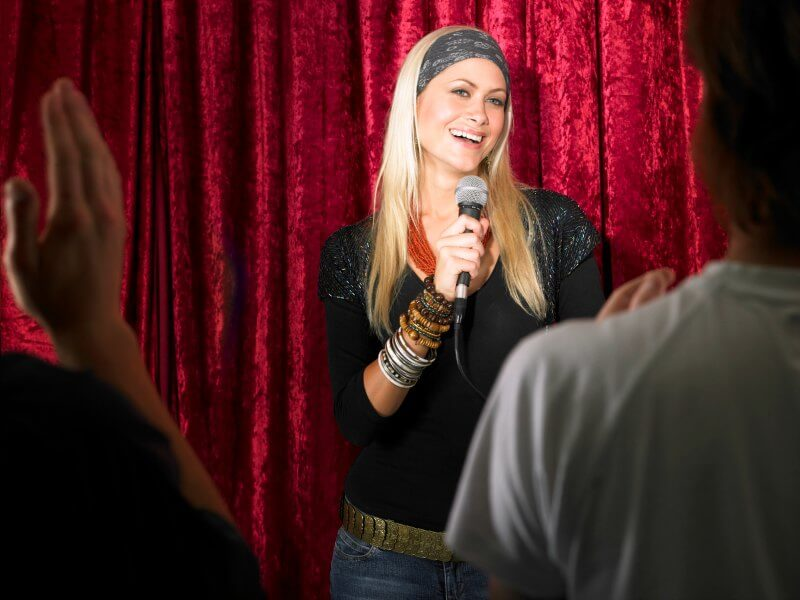 IMG: standup comedian speaking into a microphone