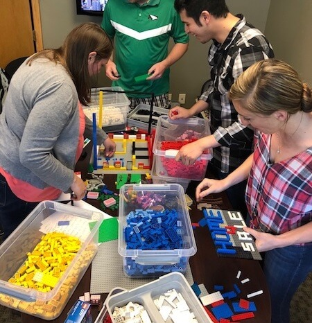 IMG: group of people working on a lego project