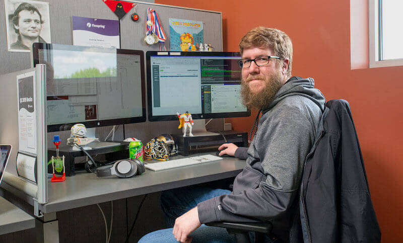 IMG: Andrew sitting at his desk at Firespring