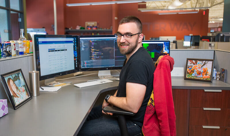 IMG: CJ sitting at his desk at Firespring